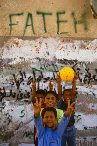 """أطفال يلعبون بجوار جدار مكتوب عليه """"فتح"""""""
