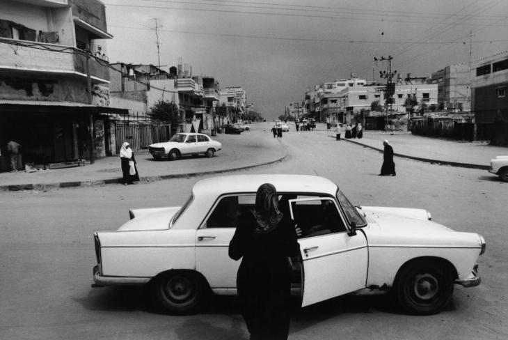 امرأة فلسطينية تهم بالركوب بإحدى السيّارات بعد اندلاع مواجهات في حي الشيخ رضوان في غزّة والمعروف بكونه دائم الاشتباك - 1993