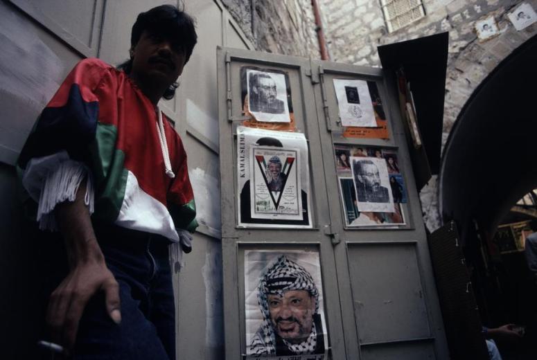رجل يقف بجوار بوسترات لعرفات 1993