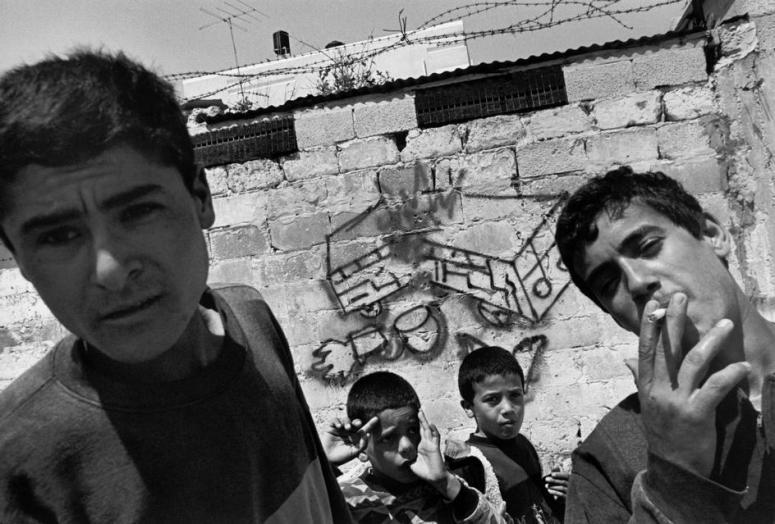 فلسطينيين قرب جدار رسم عليه جرافيتي لتفجير باص قرب مسجد لحماس