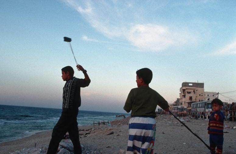 Young Palestinian boys practice using slings at a beach in Gaza Strip.